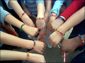 Student hands wearing solar beads.